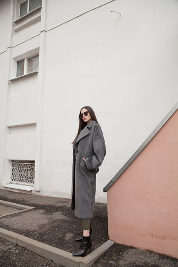Full length side view portrait of young woman in grey coat and suit against wall outdoors, outwear