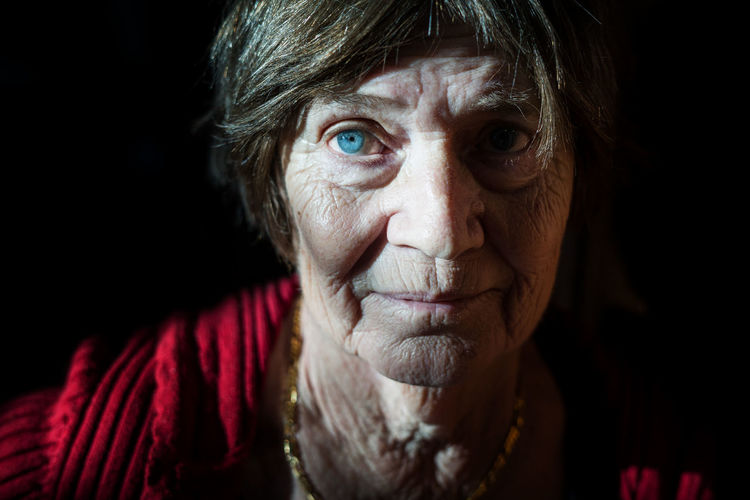 Close-up portrait of senior woman against black background