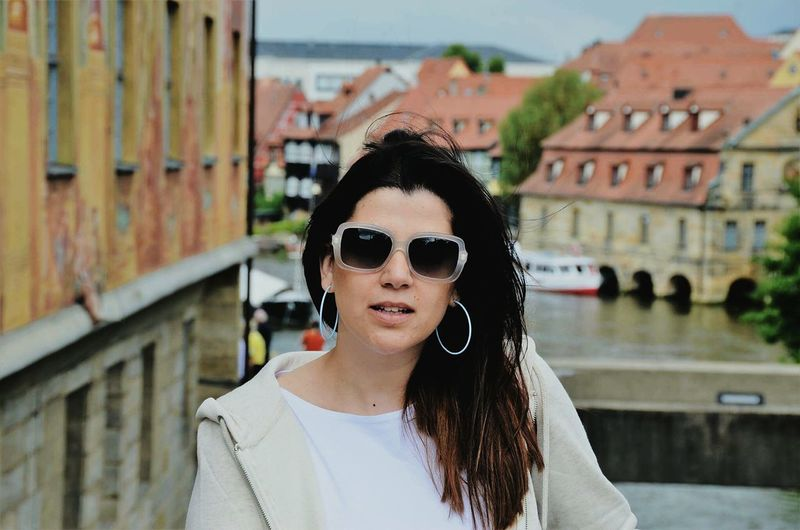 Portrait of woman wearing sunglasses against buildings in city