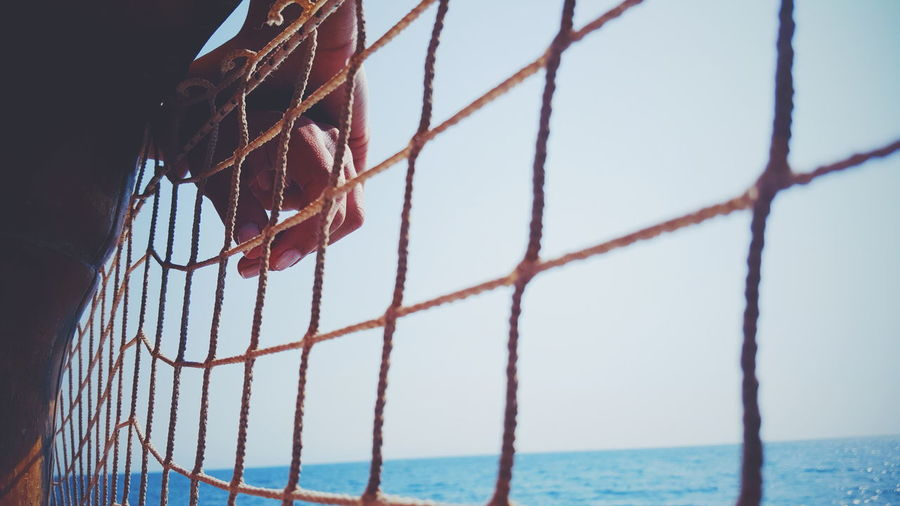 Cropped Image Of Hands On Net By Sea Against Clear Sky