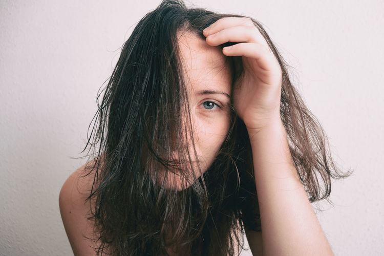 Portrait of young woman with messy hair against wall