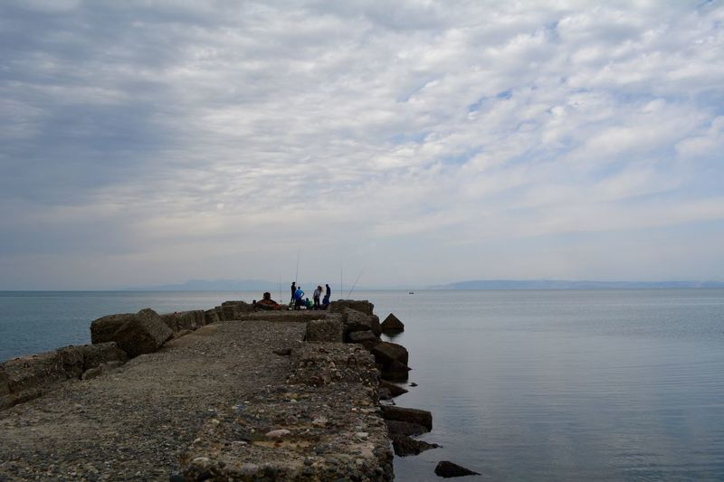 People On Rocks By Sea Against Cloudy Sky
