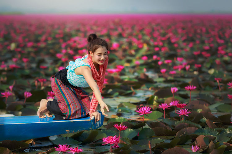 Full Length On Woman Reaching Pink Flower In Pond