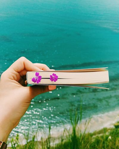 Close-Up Of Woman Hand Holding Flower In Book Against Sea
