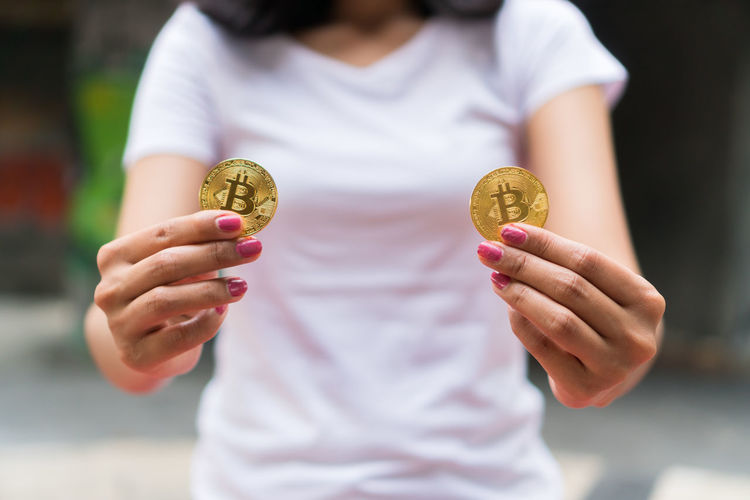 Midsection of woman holding bitcoin