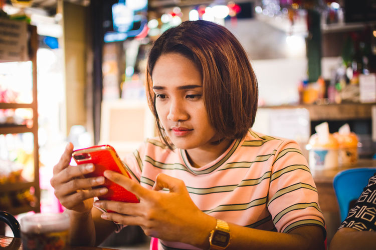 Casual Clothing Connection Focus On Foreground Front View Hairstyle Headshot Holding Indoors  Leisure Activity Lifestyles Mobile Phone One Person Portable Information Device Portrait Real People Restaurant Sitting Smart Phone Technology Telephone Wireless Technology