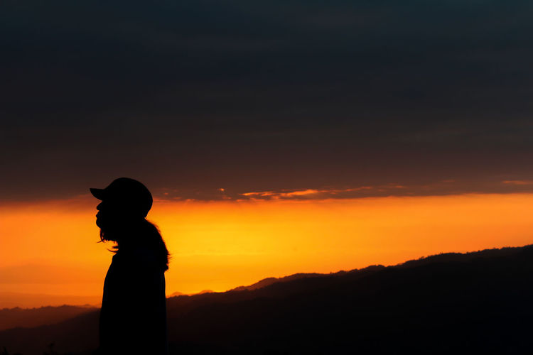 Silhouette man standing against orange sky during sunrise