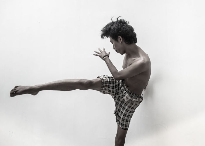 Shirtless young man kicking while standing against white background