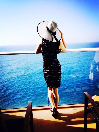 Rear view of beautiful woman standing at ship balcony by sea against sky