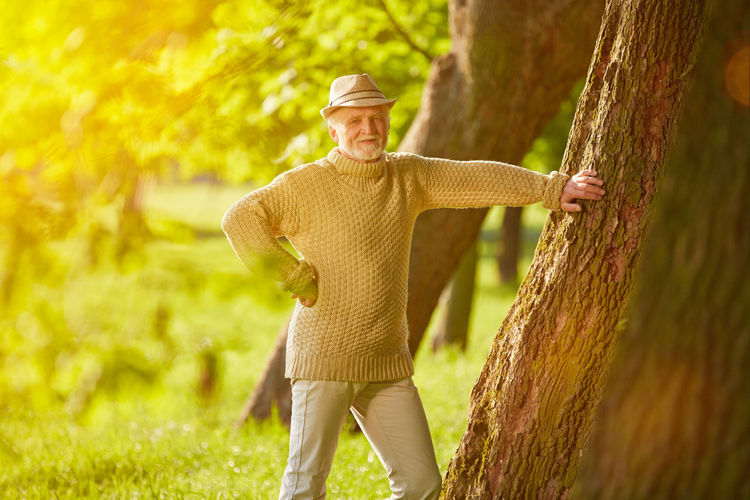 Man Standing By Tree Trunk At Park