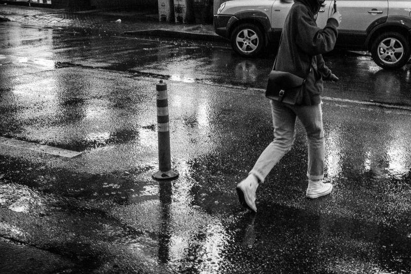 Man standing on wet street during rainy season
