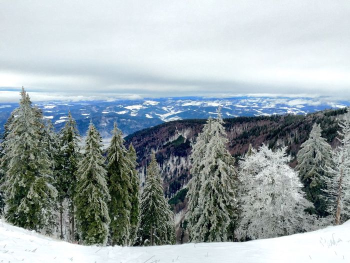 Scenic view of snow covered mountains against cloudy sky