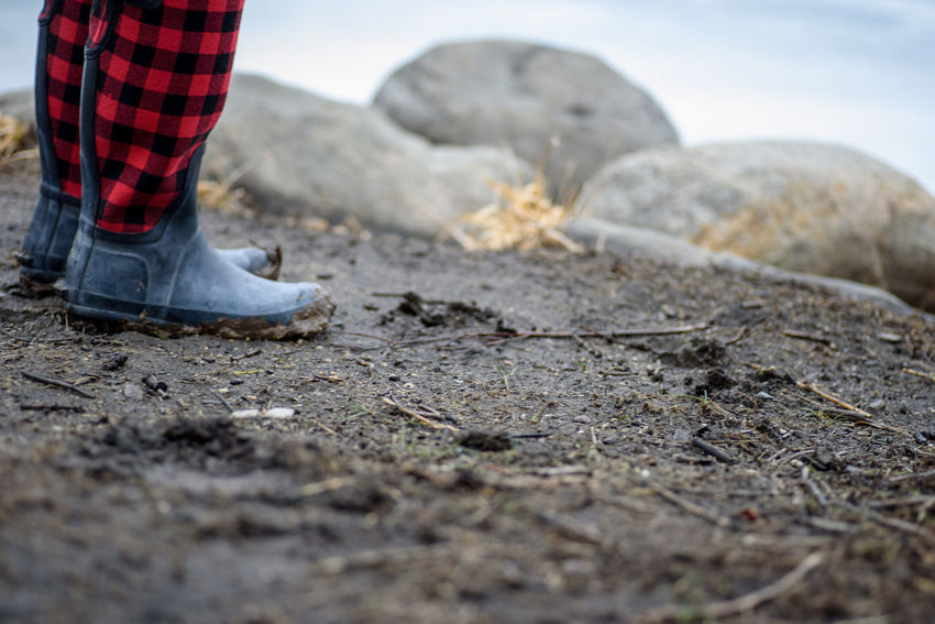 closeup of woman wearing red buffalo plaid muddy boots standing along shore Lakefront Standing Wellies  Adult Buffalo Check Buffalo Plaid Day Ground Level View Low Section Mud Muddy Boots Nature One Person One Woman Only Only Women Outdoors People Rainy Day Red Plaid Rocks Rubber Boots Shore Shoreline Young Adult