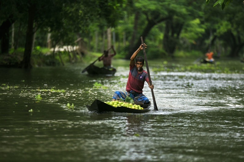 Man sitting on boat in river