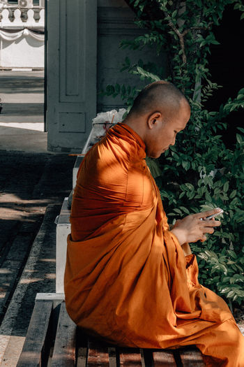 Monk using mobile phone while sitting on seat