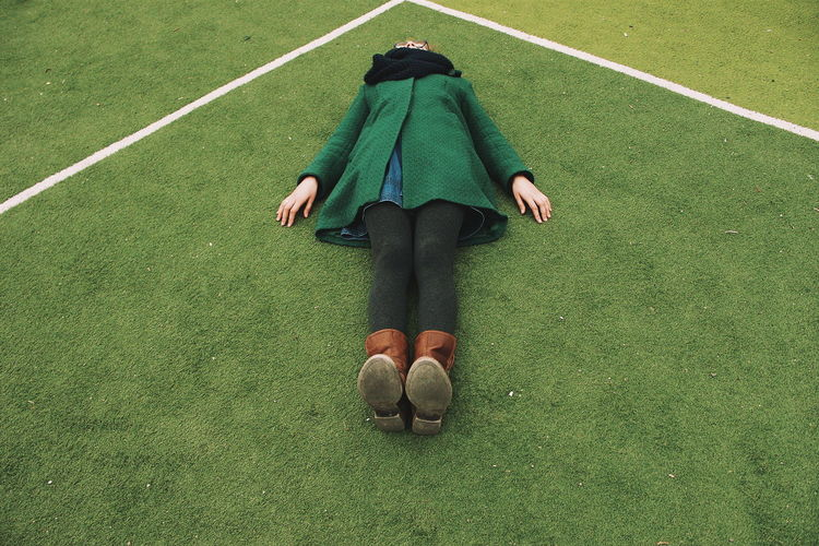 High angle view of woman lying on playing field