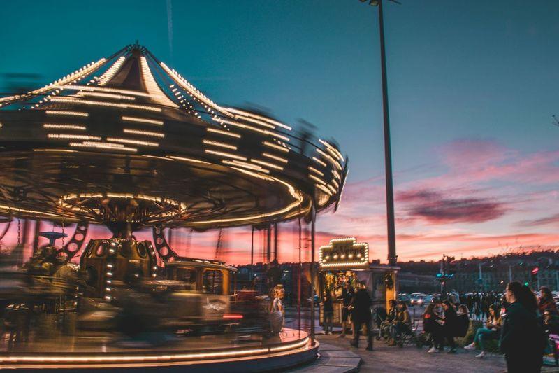 People at amusement park against sky at dusk