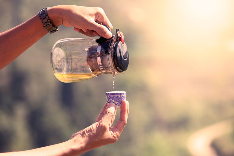 Tea jug pouring tea water into a cup in the morning time in vintage color filter Nature Pouring Tea Adult Body Part Container Cup Day Drink Finger Glass Hand Holding Human Body Part Human Hand Human Limb Jug Lifestyles Nature Outdoors Real People Refreshment Water