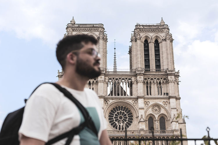 Man standing against church in city