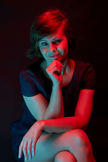Portrait of smiling woman sitting against black background