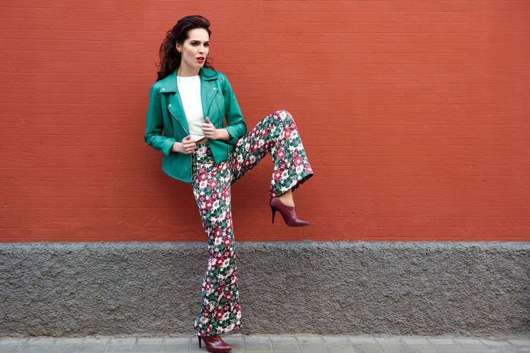 Young brunette woman, model of fashion, wearing green modern jacket and flower pants on red wall. Pretty caucasian girl with long wavy hairstyle. Female with red lips in urban background. Fashion Adult Architecture Beautiful Woman Beauty Built Structure Casual Clothing Day Fashion Front View Full Length Hairstyle Lifestyles Looking At Camera One Person Outdoors Portrait Real People Smiling Standing Wall - Building Feature Women Young Adult Young Women