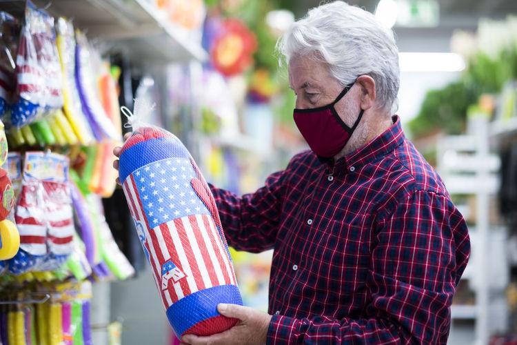 Senior man wearing mask holding punching bag at store