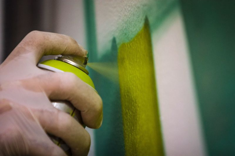 Close-up of hand painting wall with spray paint