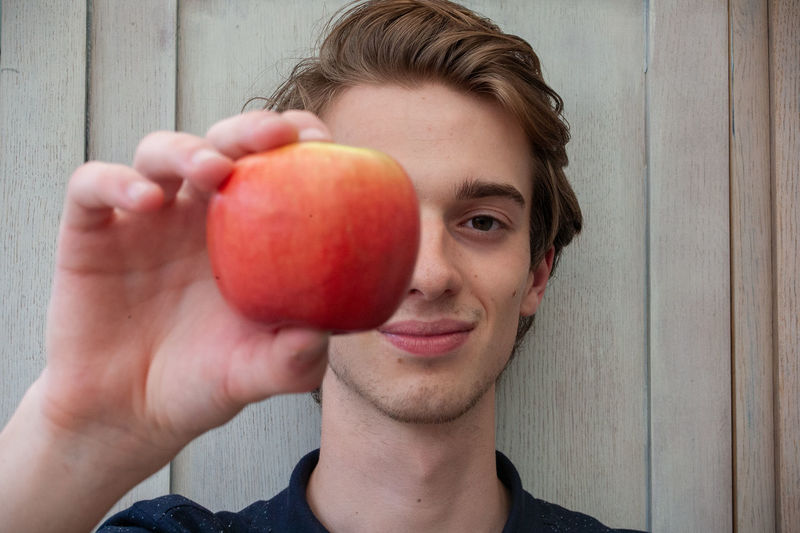 Portrait of young man holding apple