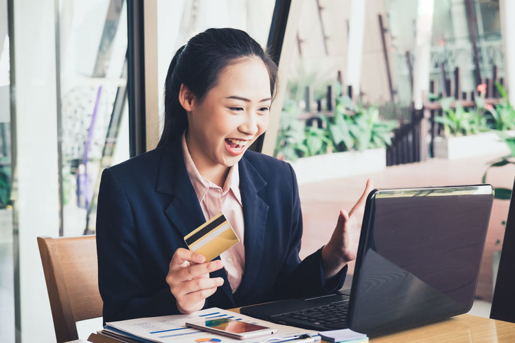 Young Woman Holding Credit Card While Shopping On Laptop In Office