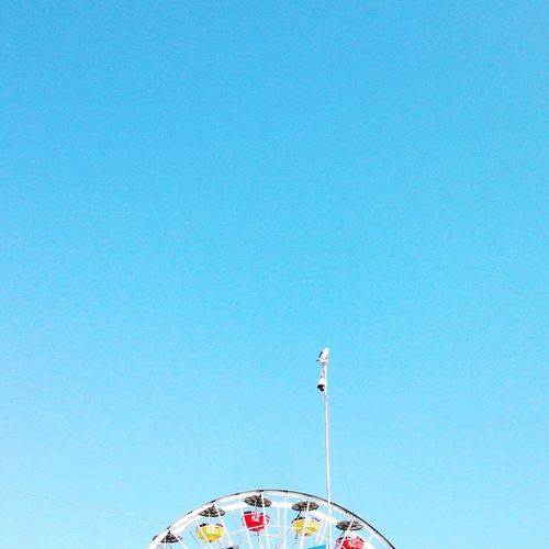 Low angle view of carousel against clear blue sky
