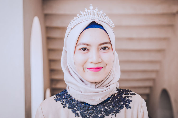 Portrait of smiling young woman headscarf and tiara