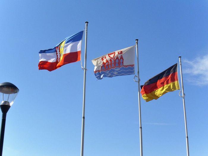 Schleswig-Holstein, Heiligenhafen und Deutschlandflagge Blue Clear Sky Day Deutschlandflagge Flag Flag Pole Flaggen Flaggenmaste Flattern Fluttering Heiligenhafenflagge Low Angle View No People Outdoors Patriotism Pride Red Schleswig-Holstein Sky Stolz Sein Striped Waving Wind