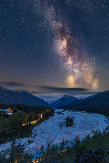 Scenic view of landscape and snowcapped mountains against star field in sky at night