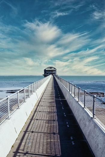 View of boardwalk leading towards sea against sky