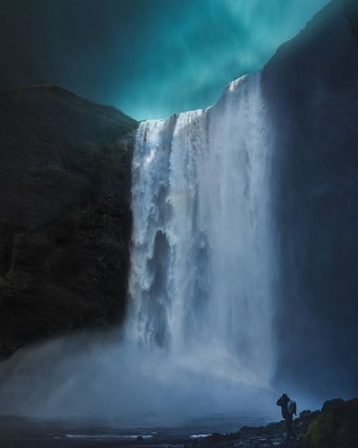 Scenic View Of Waterfall Falling From Mountain At Night