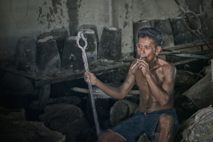 Full length of man sitting on rock