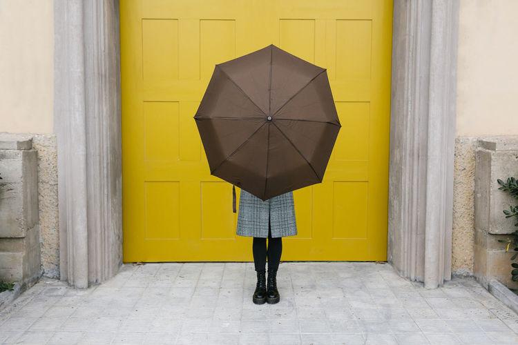 Woman standing by yellow door of building