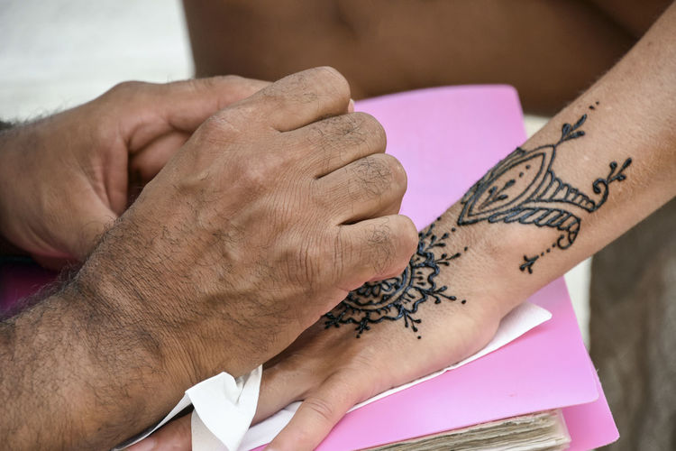 Drawing a temporary tattoo on the hand of a lady