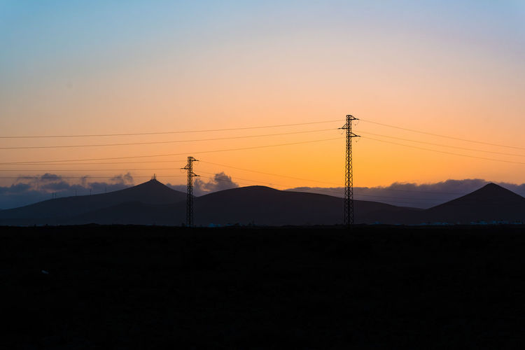 Silhouette electric pylons against sky during sunset