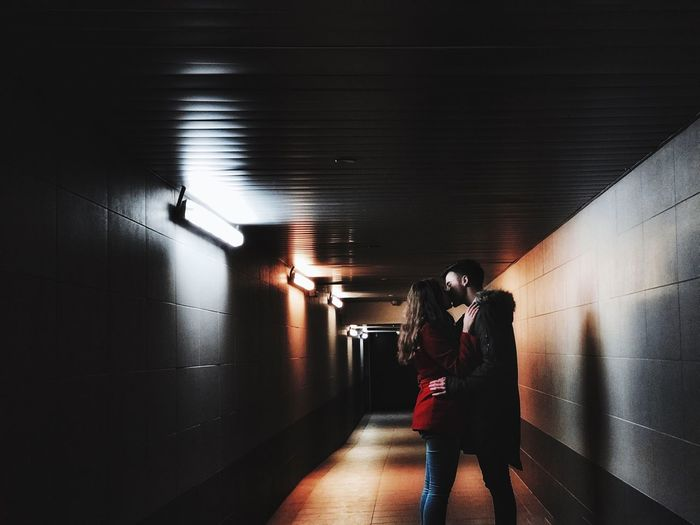 Side view of couple standing in illuminated corridor