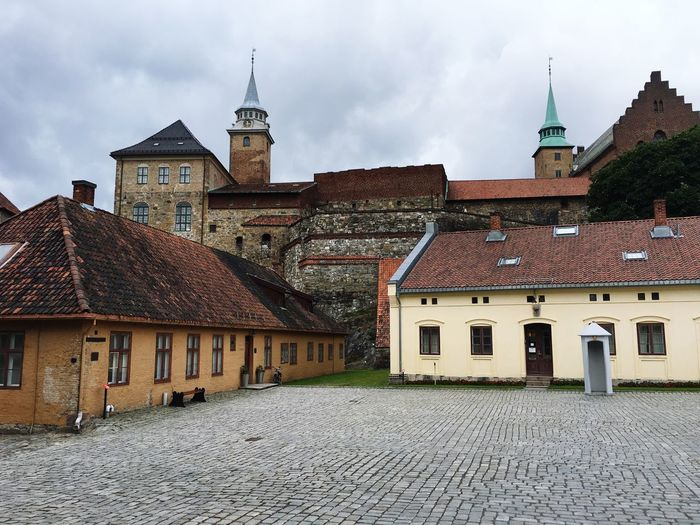 Old castle by houses against sky