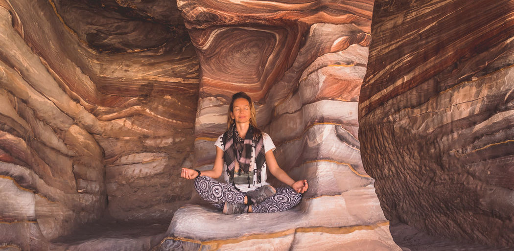 Young Woman Meditating On Rocks In Cave