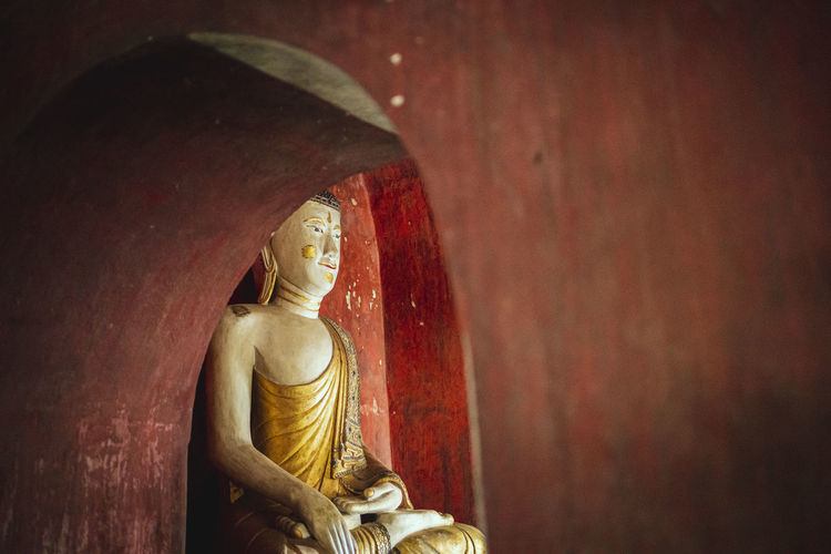 Statue of buddha against wall in building