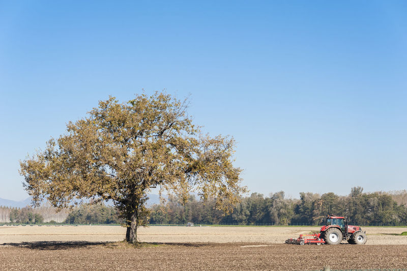 Tractor on field against clear sky
