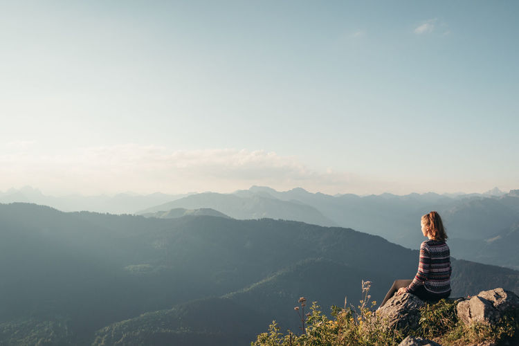 Rear view of woman sitting on mountain against sky