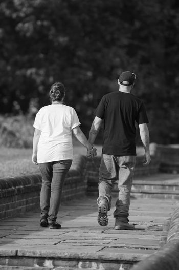 Couple Walking Through a Park Holding Hands in Black and White Black & White Couple Holding Hands Man Relationship Woman Black And White Bonding Friendship Full Length Love Outdoors People Real People Togetherness Two People Walking