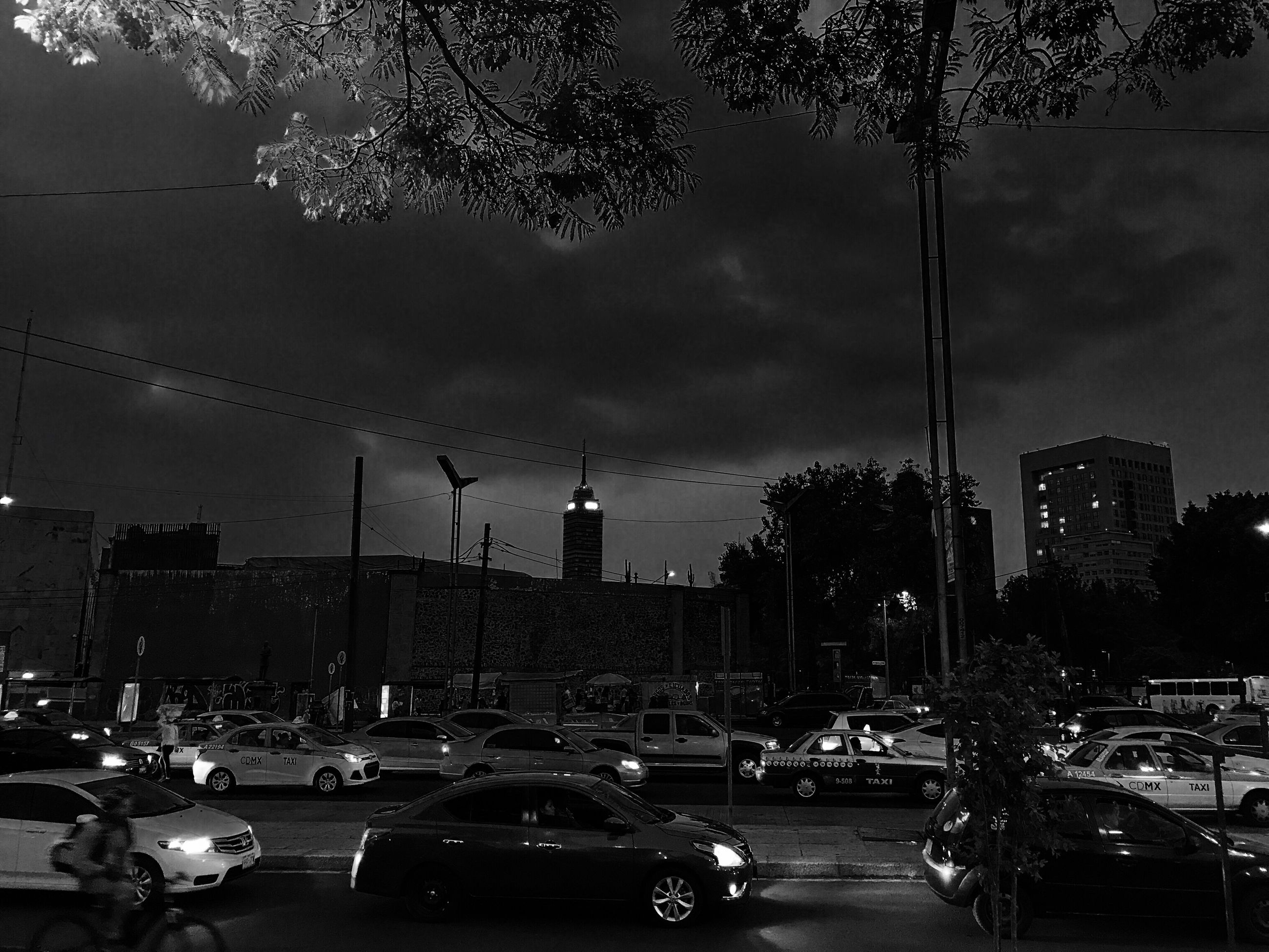 car, city, architecture, building exterior, built structure, transportation, land vehicle, road, street, traffic, illuminated, city life, sky, outdoors, tree, night, street light, cityscape, skyscraper, modern, no people