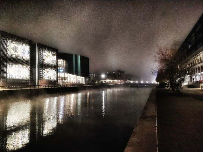 Illuminated buildings by canal against sky in city at night