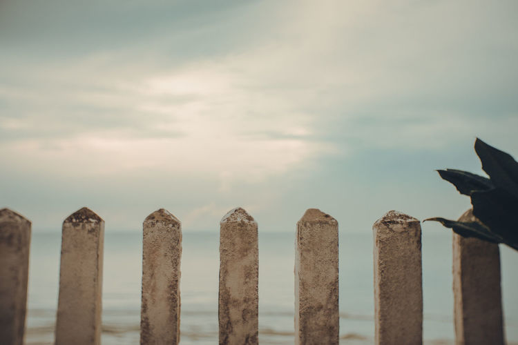 Close-up of wooden posts in sea against sky
