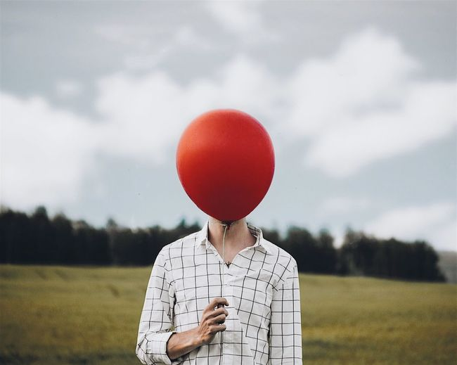 Man holding balloon on field against sky